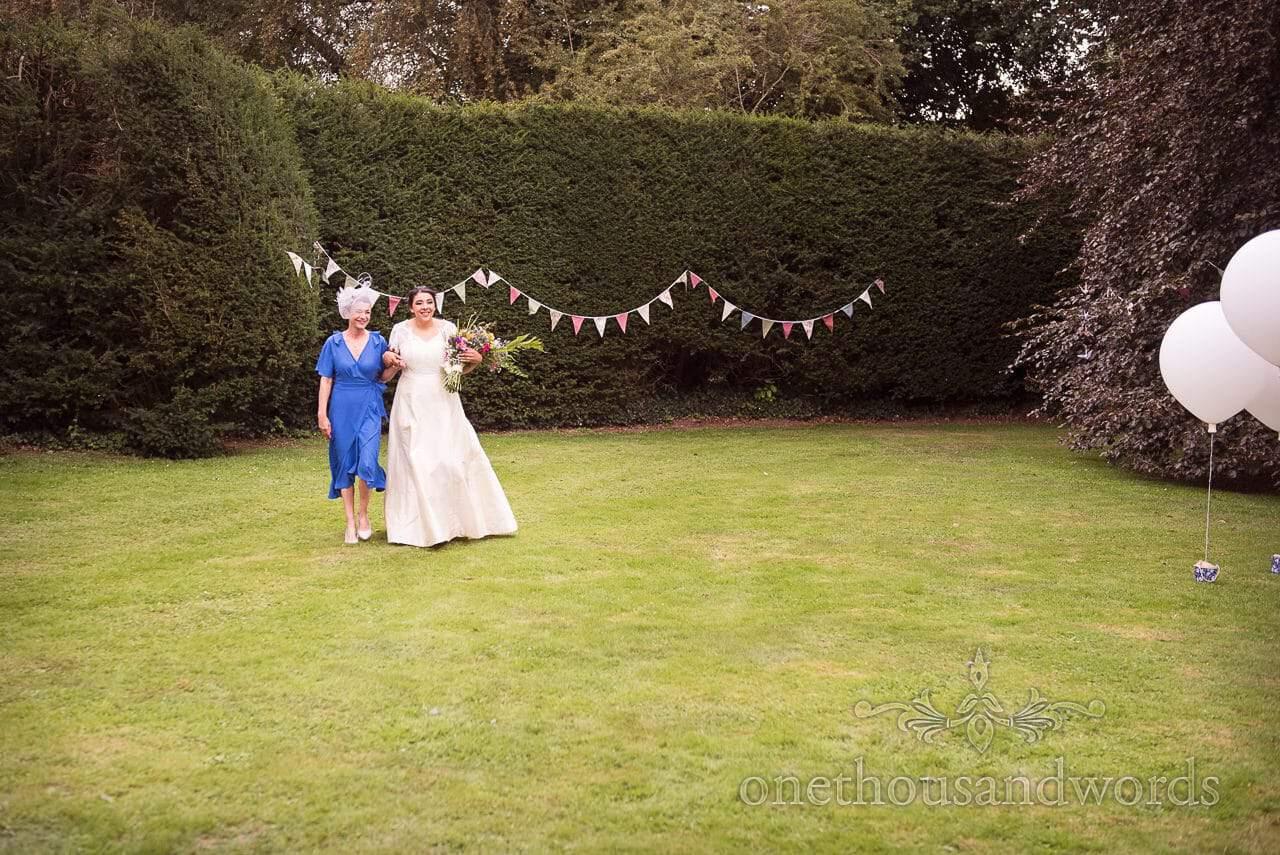 Bride is escorted by mother at Dorset garden wedding