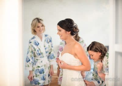 Bride is helped with her dress by bridesmaids before Italian Villa Wedding