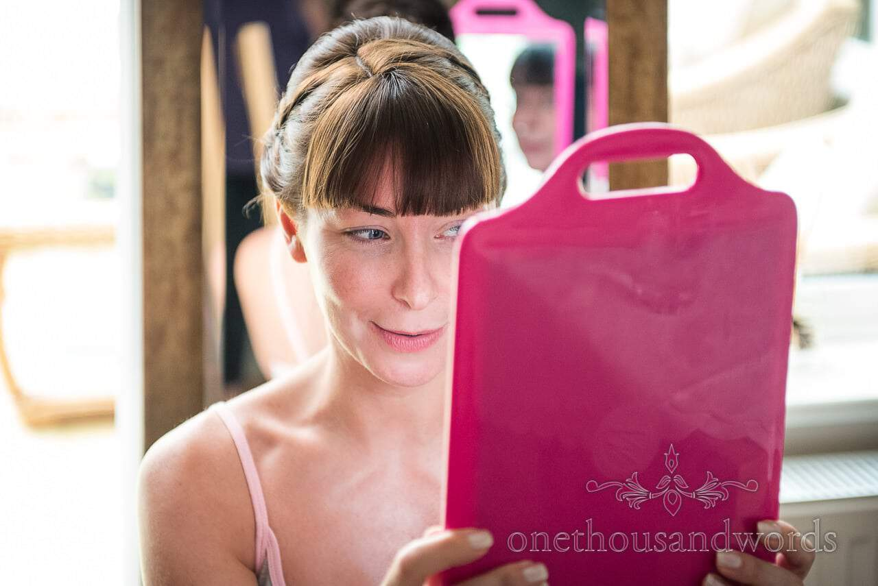 Bride looks in mirror on morning of Canford School Wedding