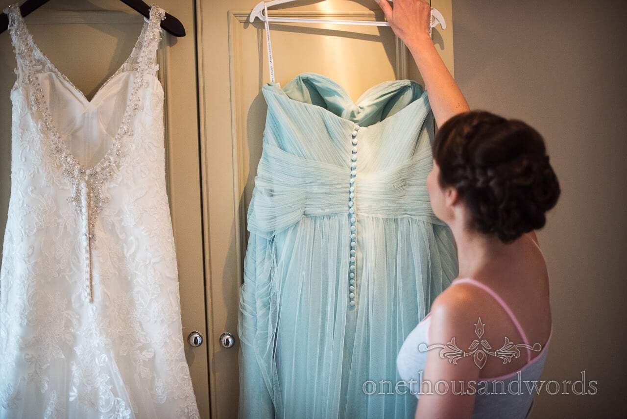 Bride reaches for bridesmaid dress from Canford School Wedding Photographs