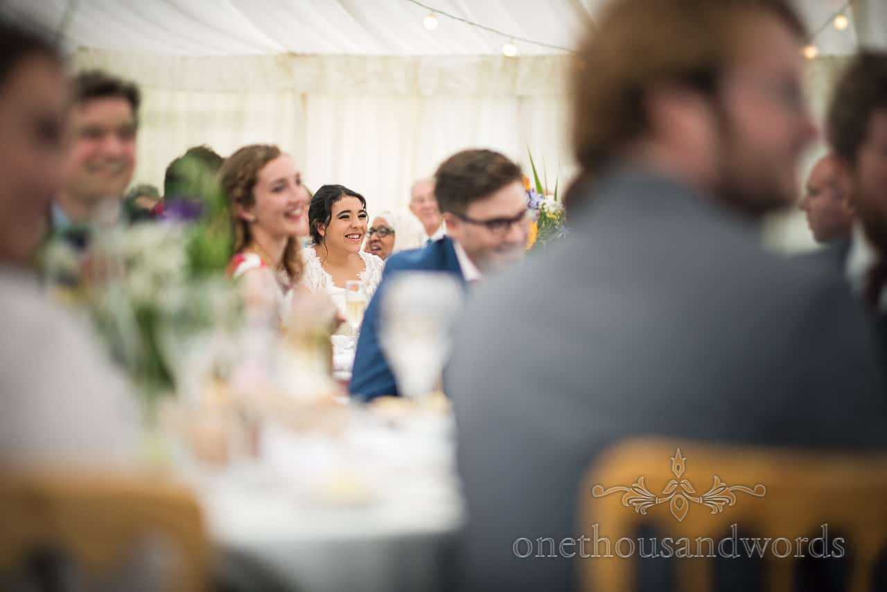 Bride reaction during speeches at garden marquee reception