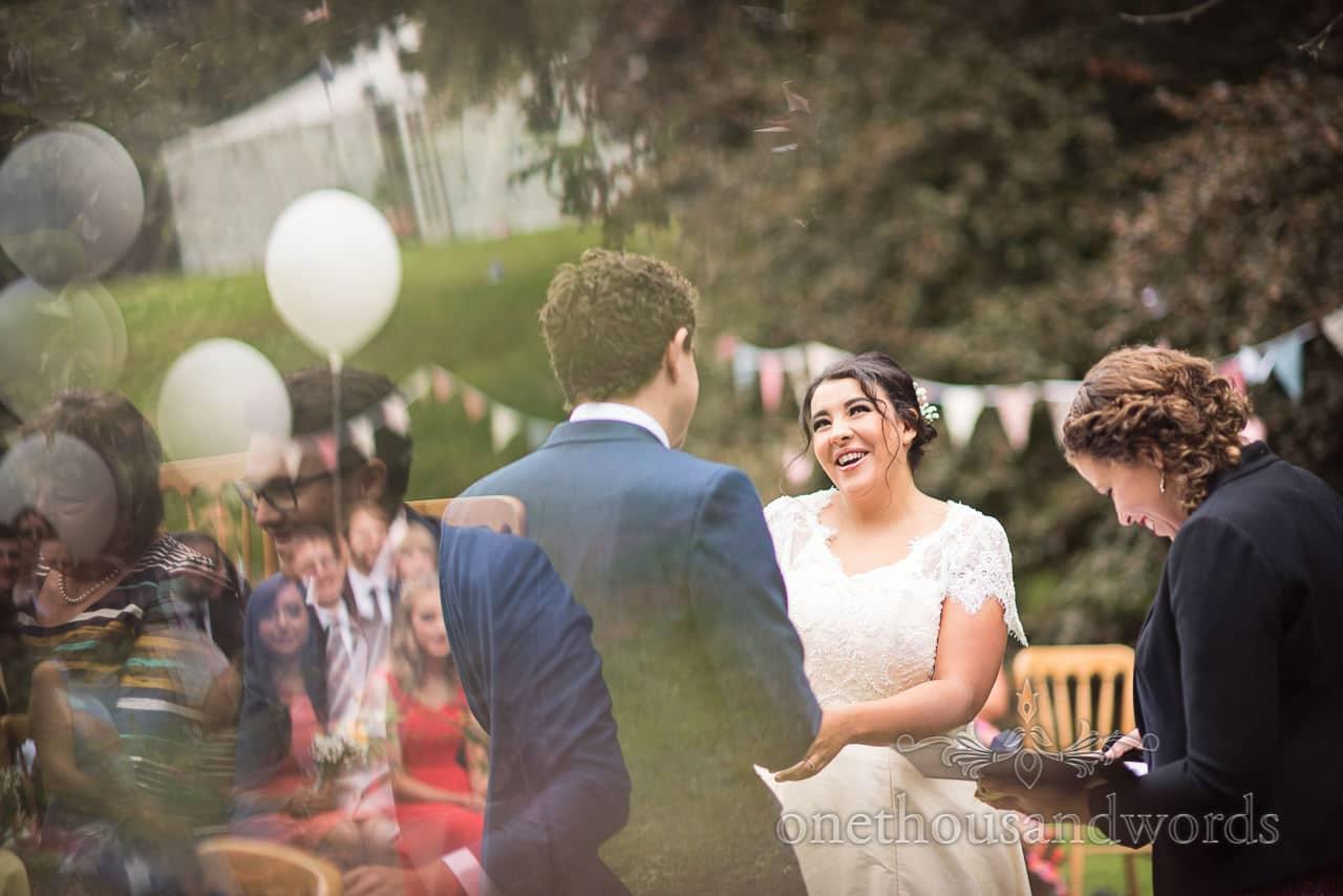 Bride smiles at groom during ceremony at Dorset garden wedding