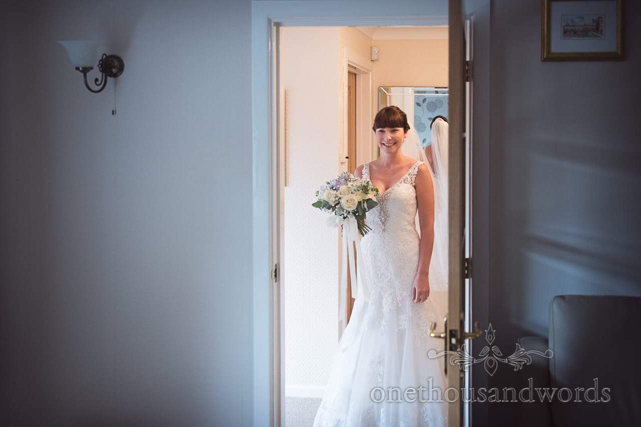 Bride with bouquet in doorway before Canford School Wedding