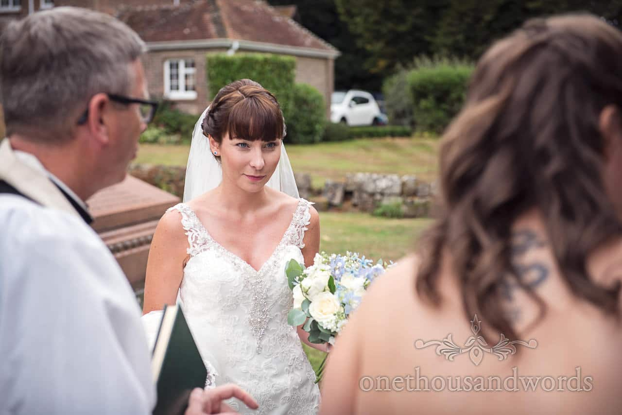 Bride with bouquet outside church before wedding at Canford School