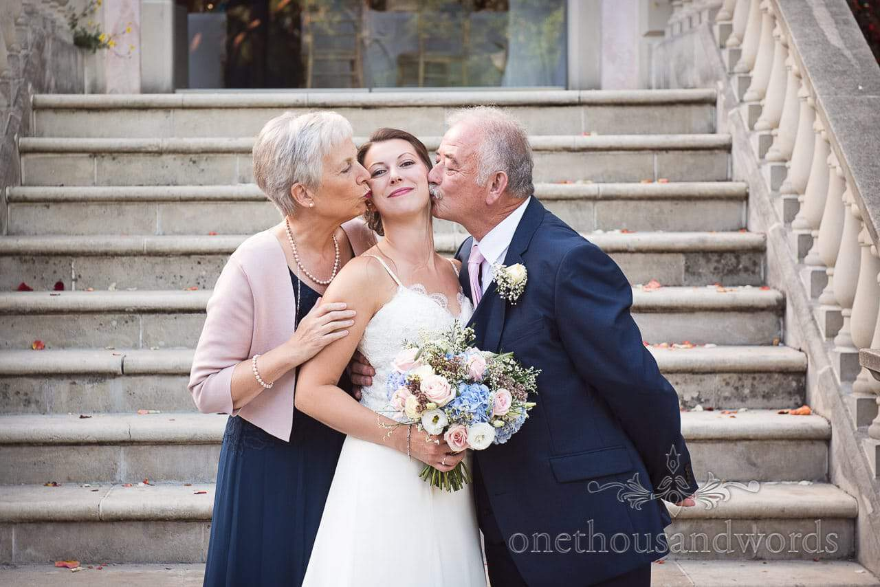 Brides parents kissing bride at Italian Villa Wedding venue photos