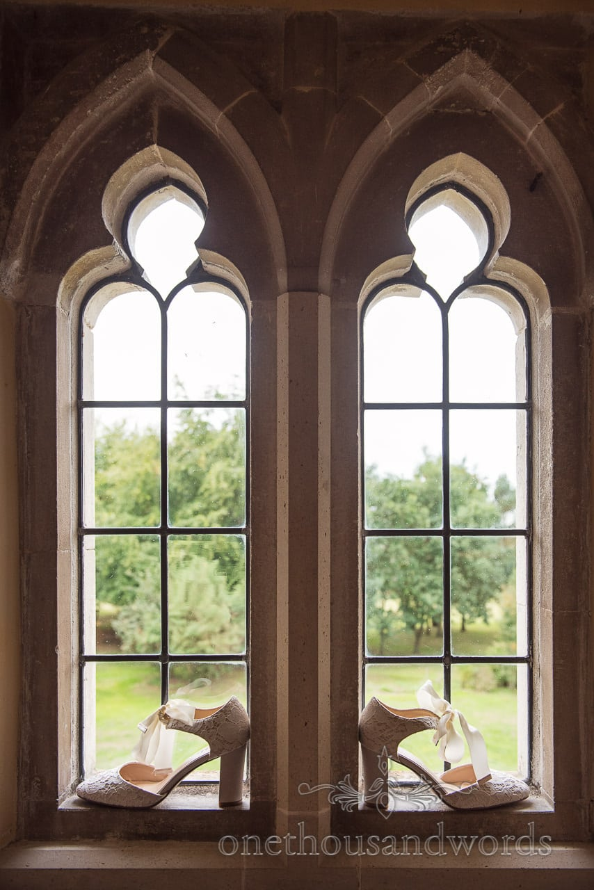 Brides wedding shoes in window at Woodsford castle before Garden Wedding