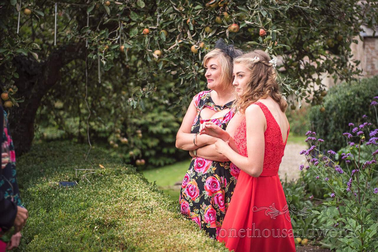 Bridesmaid and guest look on during garden wedding reception