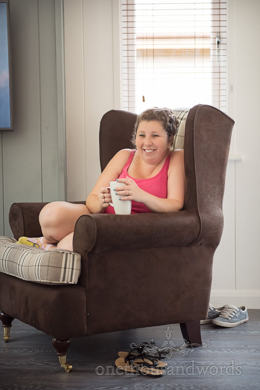 Bridesmaid enjoys a cuppa in armchair on wedding morning