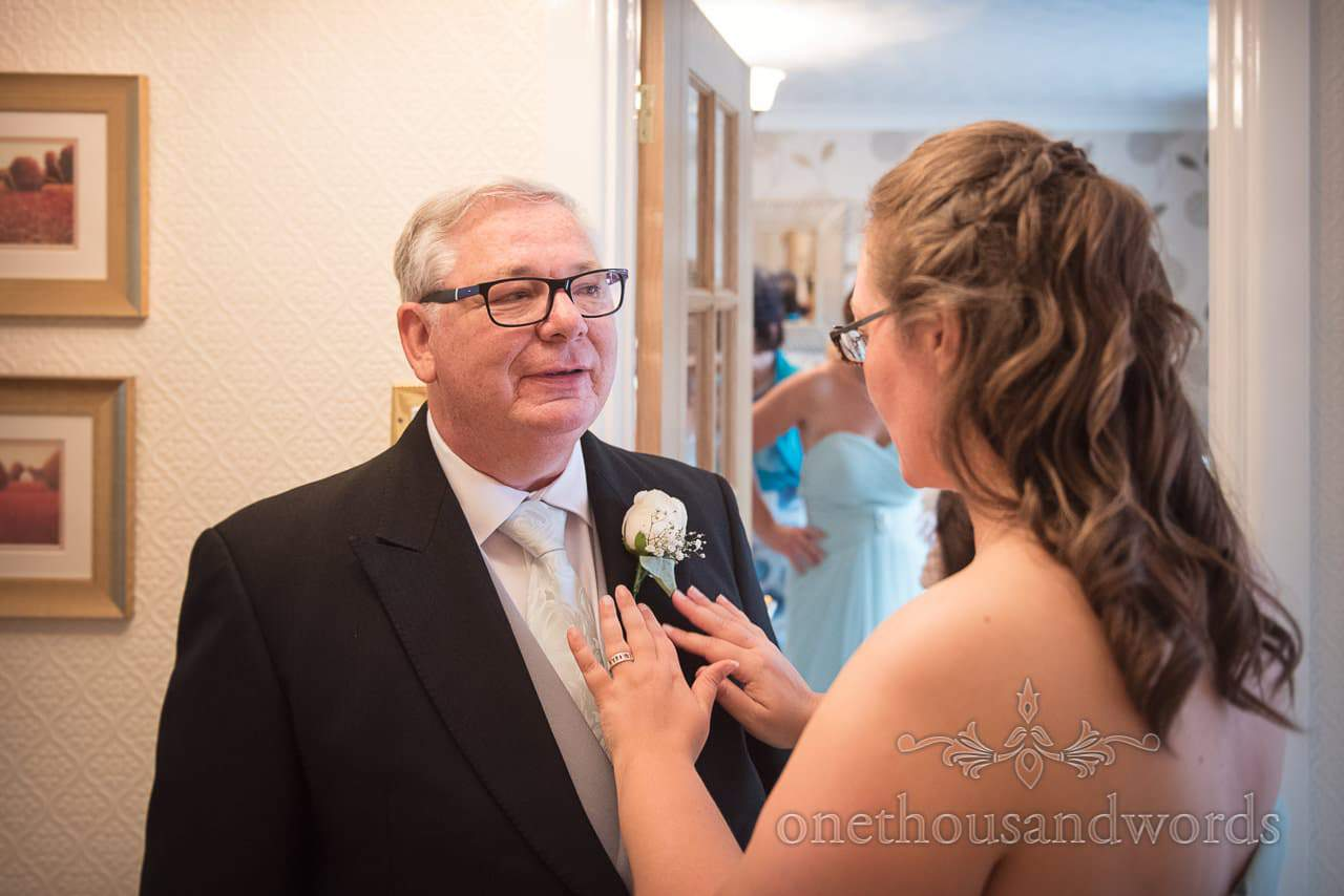 Bridesmaid fixes father of the brides buttonhole before Canford School Wedding