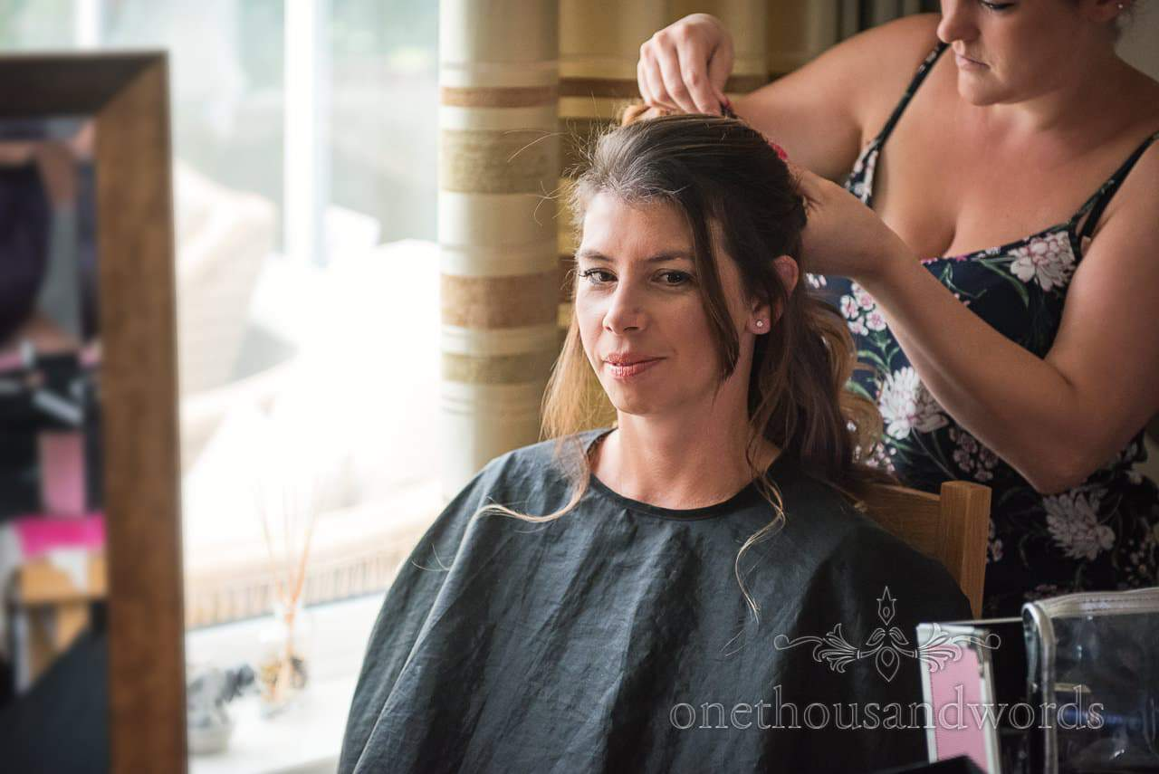 Bridesmaid has hair styled on morning of Canford School Wedding Photographs