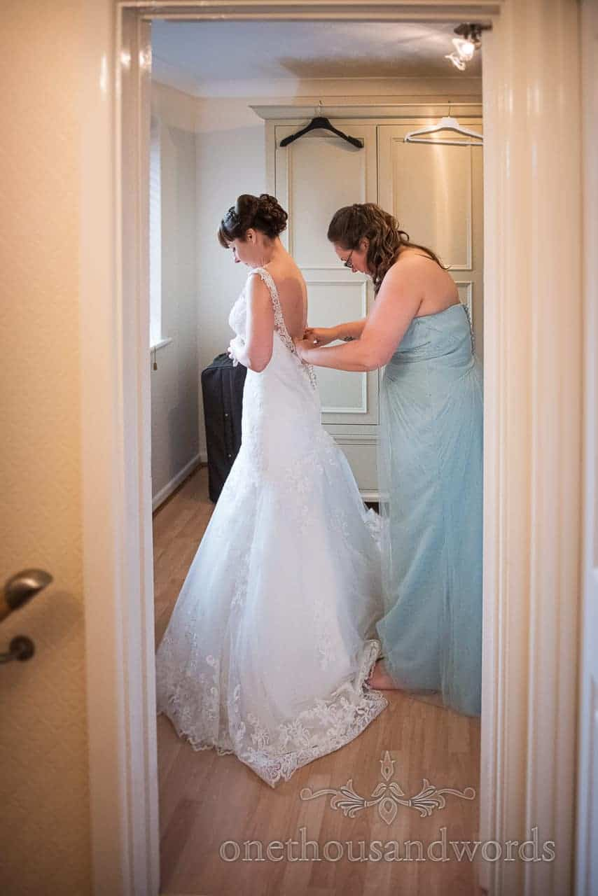 Bridesmaid helps bride with dress from Canford School Wedding