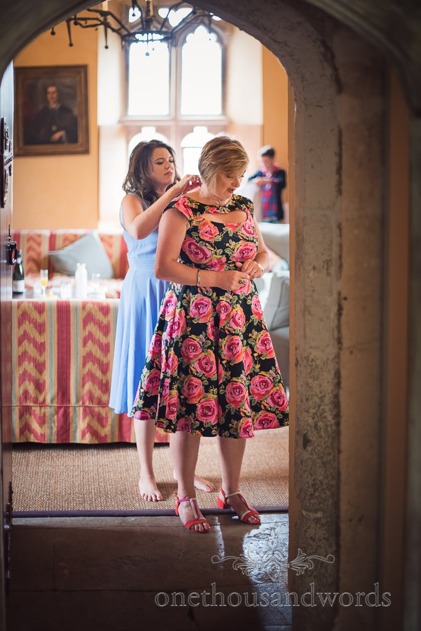 Bridesmaid helps with necklace at Woodsford castle