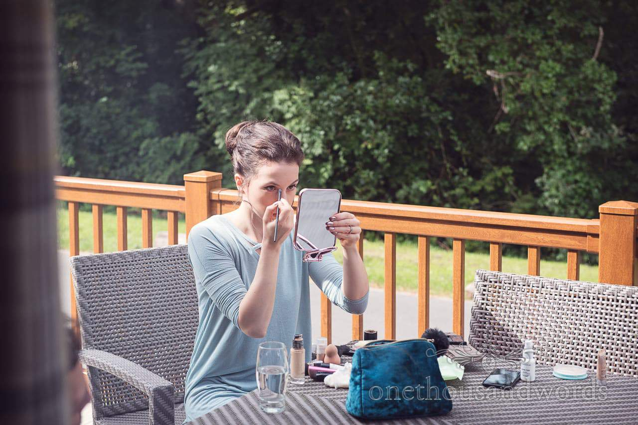 Bridesmaid does make up out side during morning preparations
