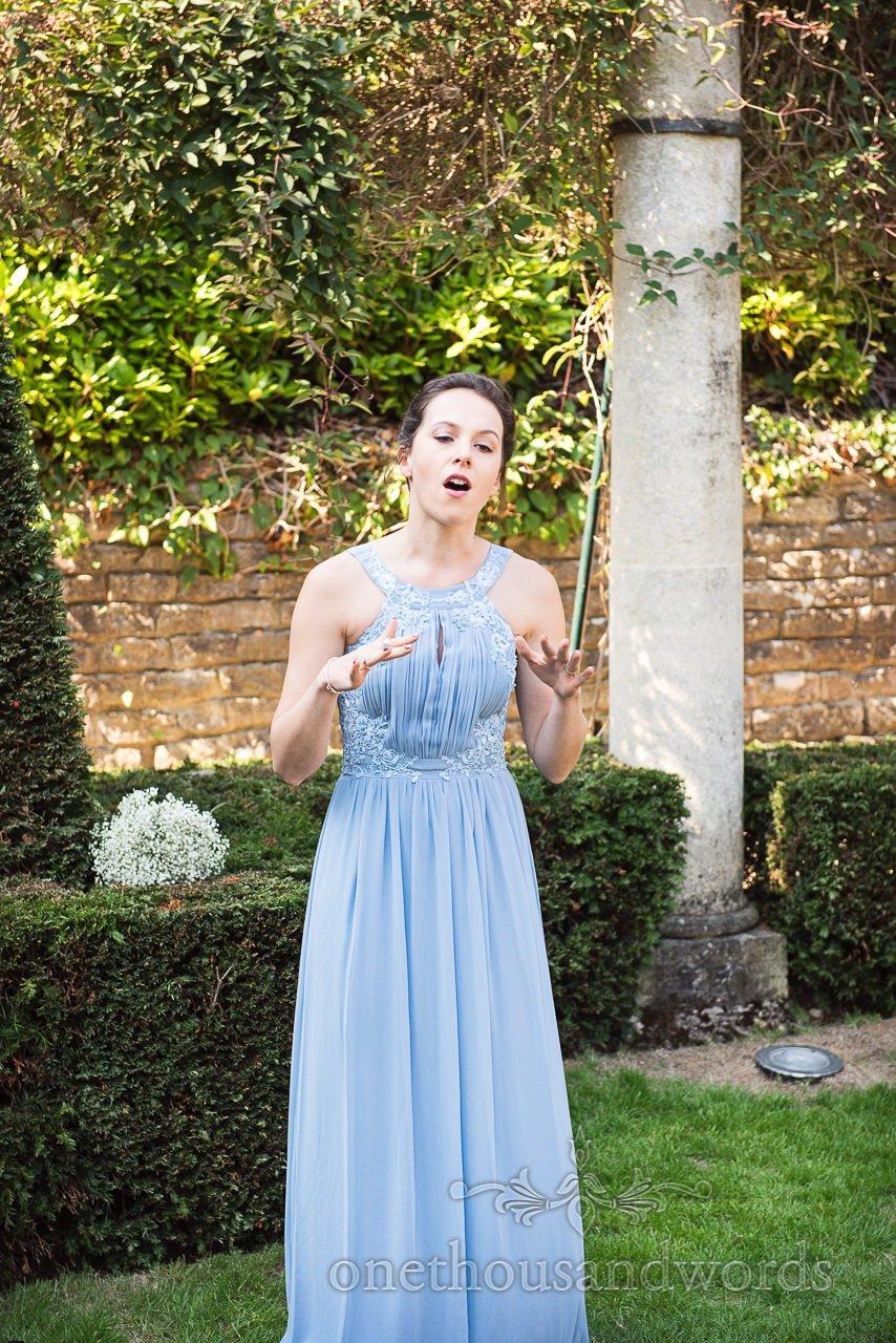Bridesmaid performs song during drinks reception at Italian Villa Wedding
