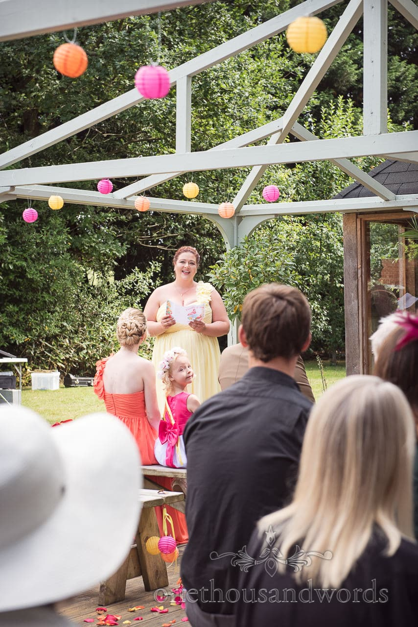 Bridesmaid sings to guests during outdoor ceremony at The Old Vicarage