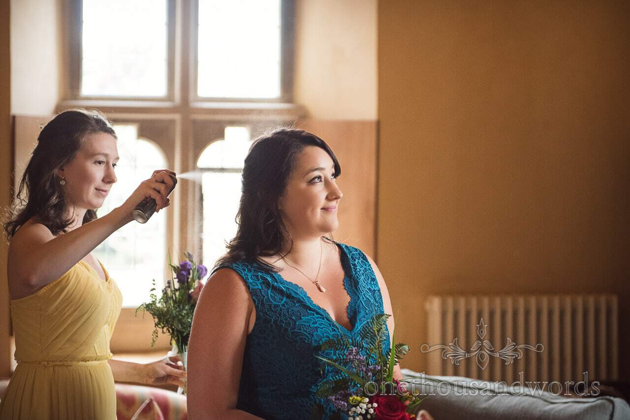 Bridesmaid sprays another bridesmaid with hair spray at Woodsford castle