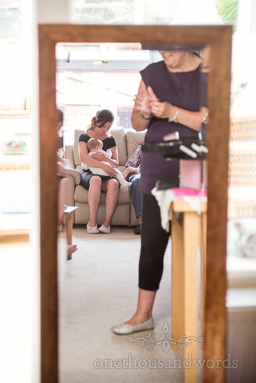 Bridesmaid with baby in mirror from morning before Canford School Wedding