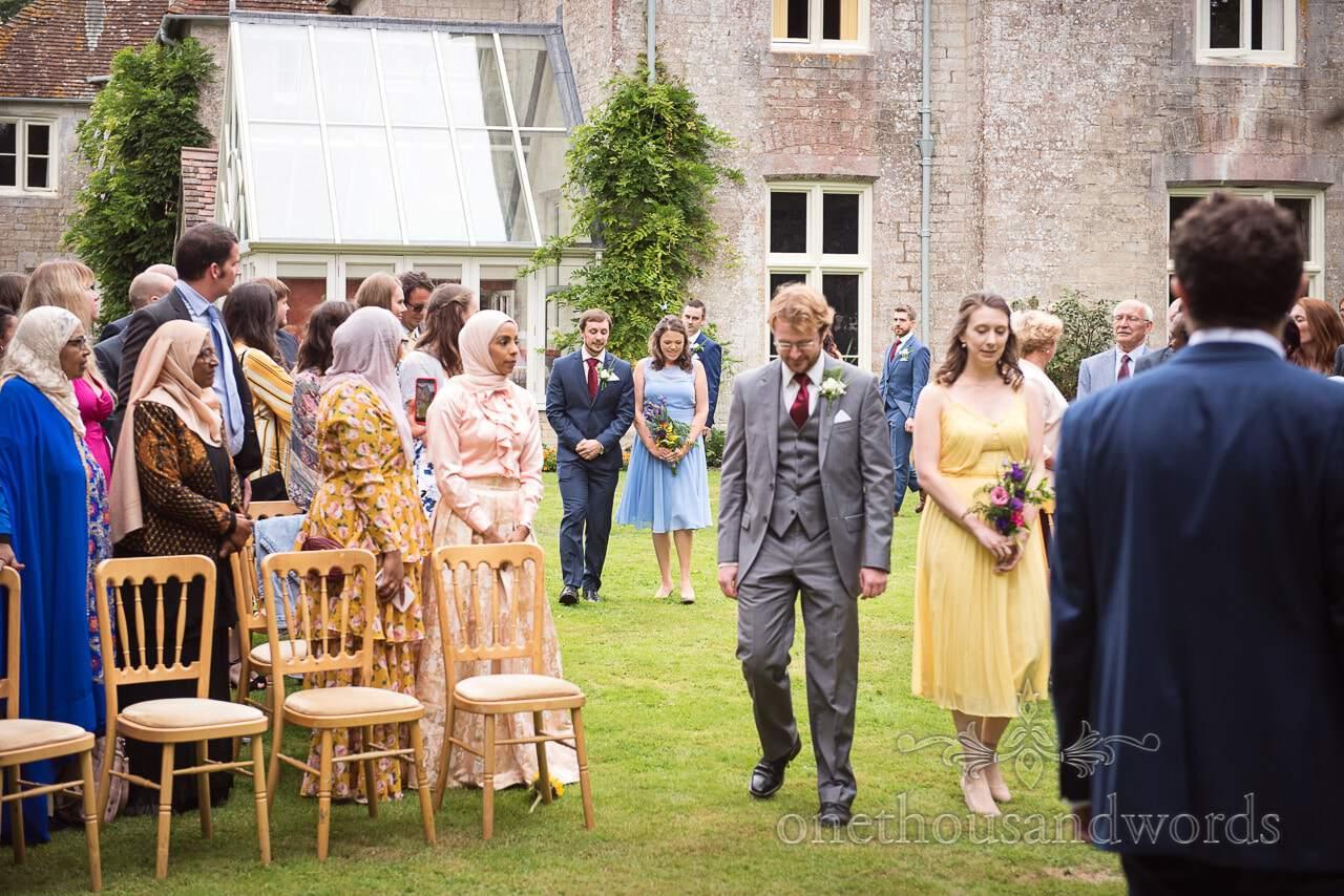 Bridesmaids escorted down the aisle by groomsmen at Dorset garden wedding