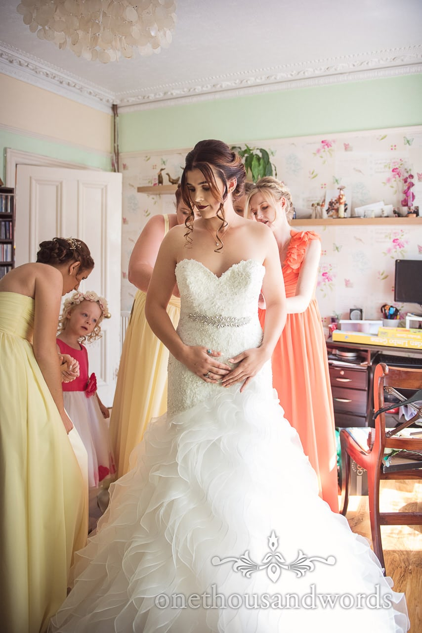 Bridesmaids help bride with dress before the Old Vicarage Wedding