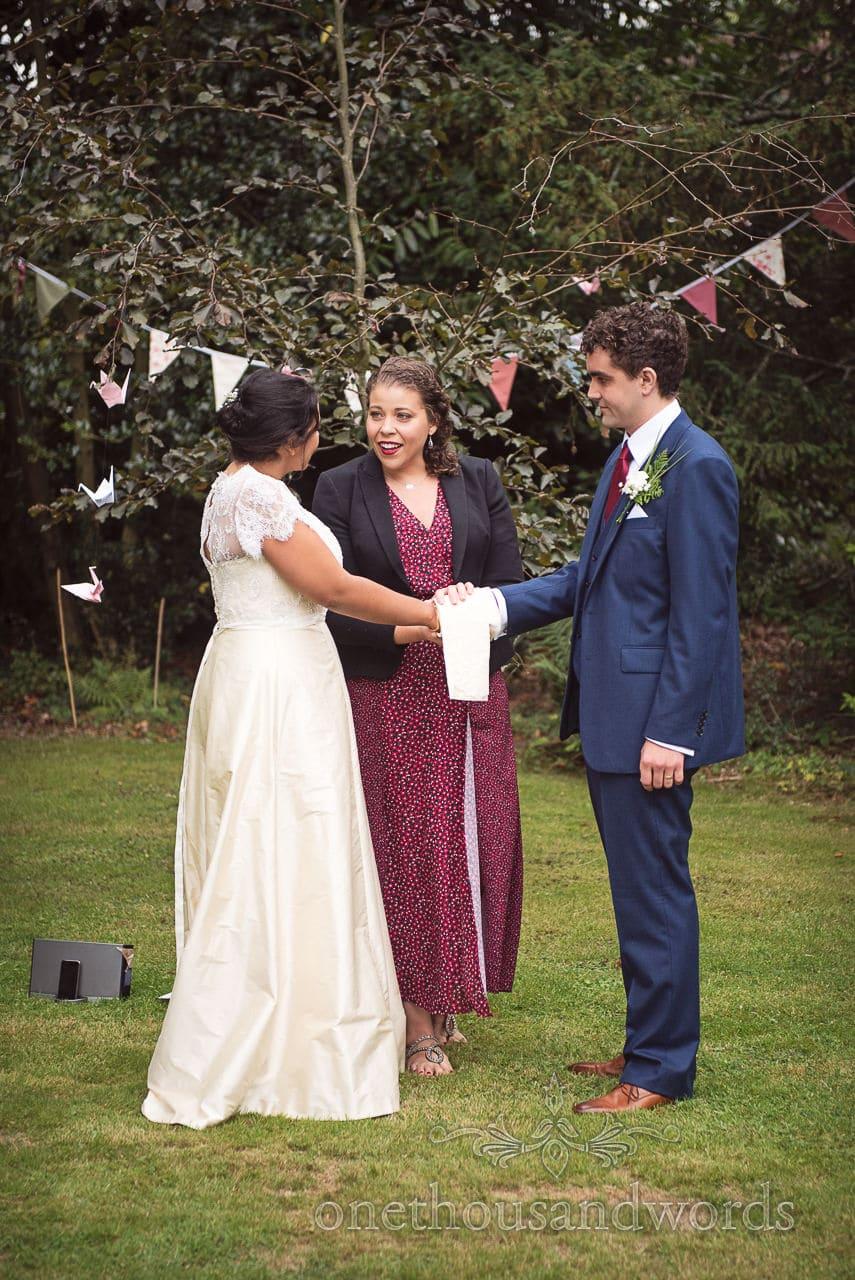 Celebrant performs hand fasting ceremony at Dorset garden wedding