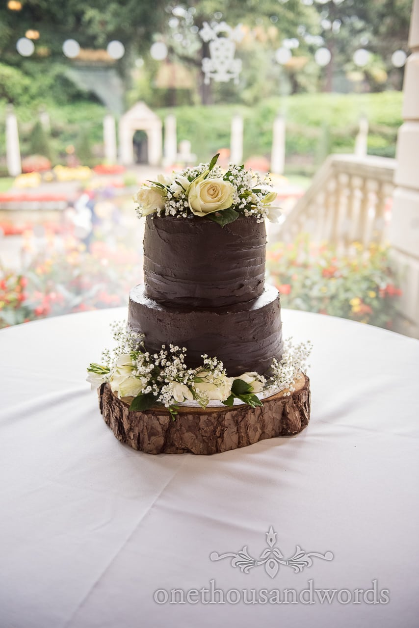 Chocolate iced brown wedding cake decorated with roses and gypsophila