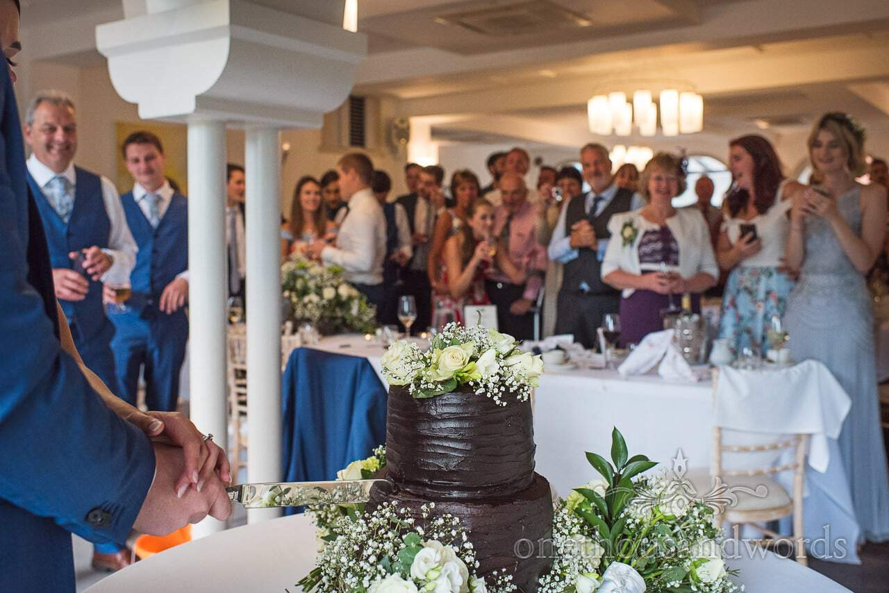 Chocolate wedding cake is cut watched by guests at Italian Villa Wedding venue