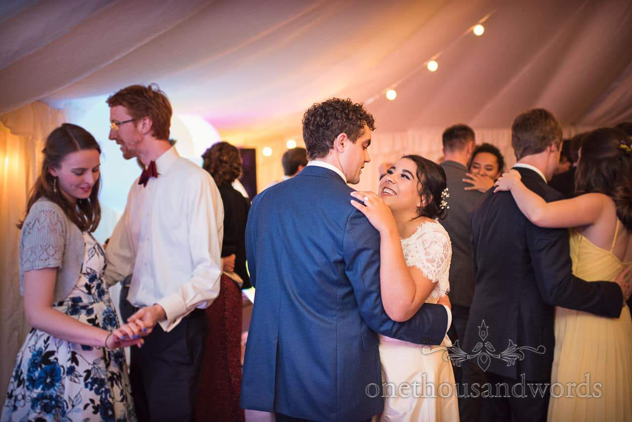 Dancing bride and groom are joined by guests during marquee wedding reception