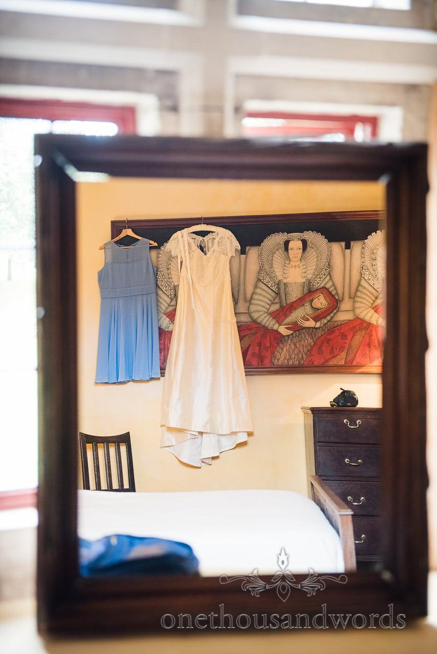 Designer wedding dress hangs on painting at Woodsford castle before Garden Wedding