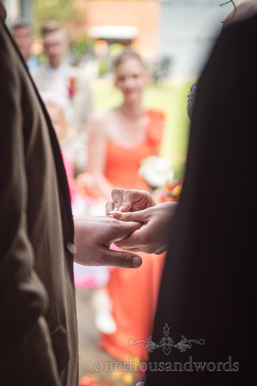 Exchange of rings while bridesmaid looks on at The Old Vicarage Wedding