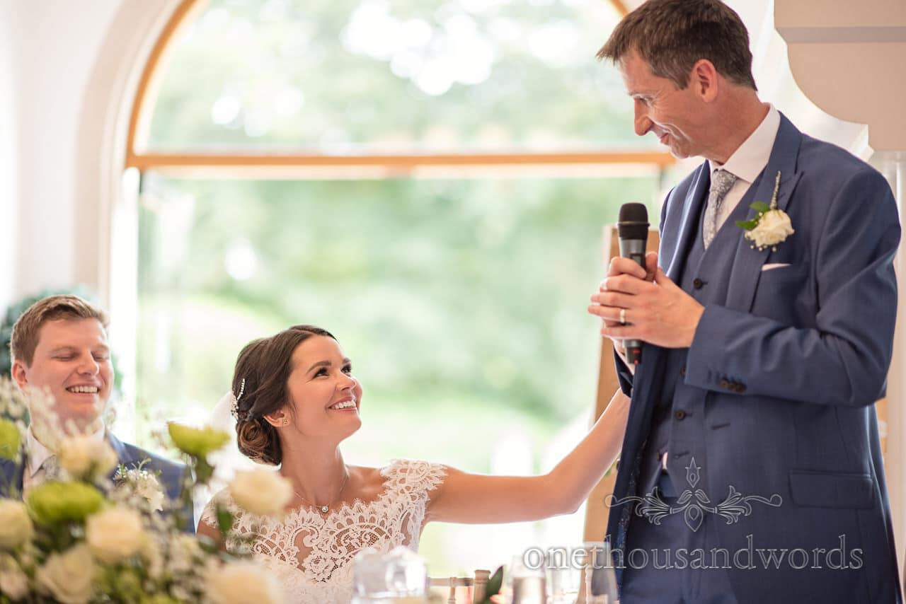 Father of the bride is touched by smiling bride during his wedding speech