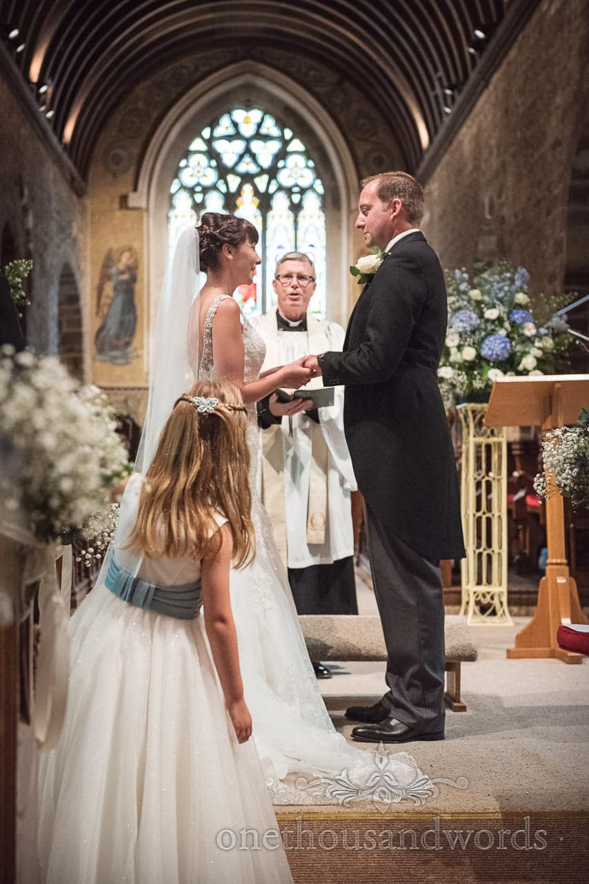 Flower girl looks on during ring exchange at Norman church wedding at Canford School