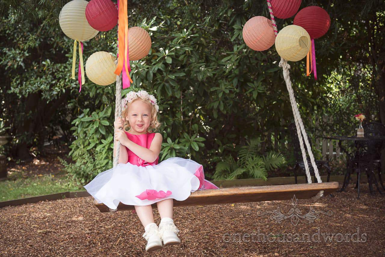 Flower girl on garden swing at The Old Vicarage Wedding