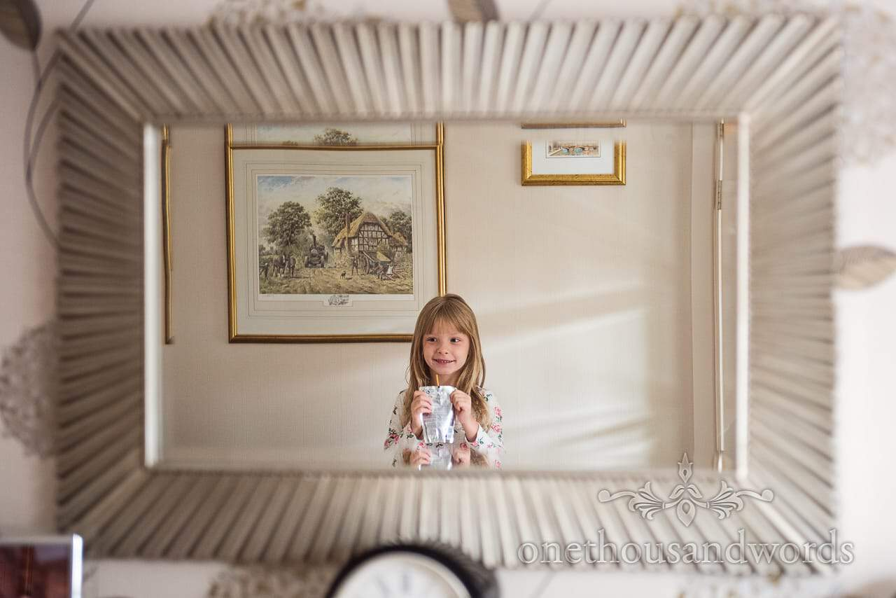Flower girl reflection in mirror from morning of Canford School Wedding