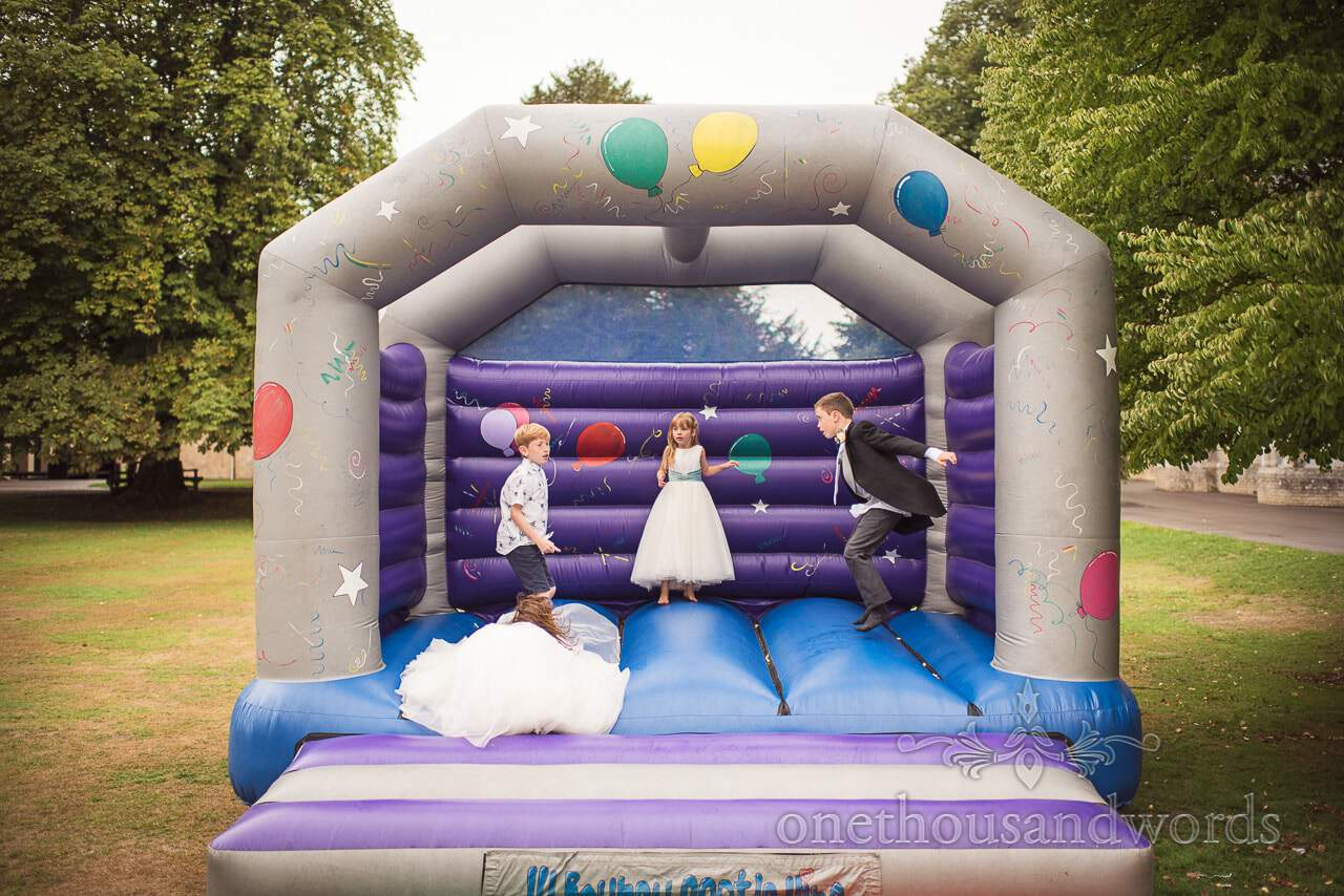 Flower girls and young wedding guests enjoy bouncy castle at reception