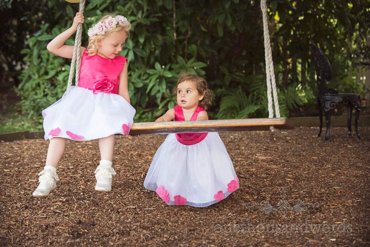 Flower girls play on garden swing at The Old Vicarage Wedding Photographs