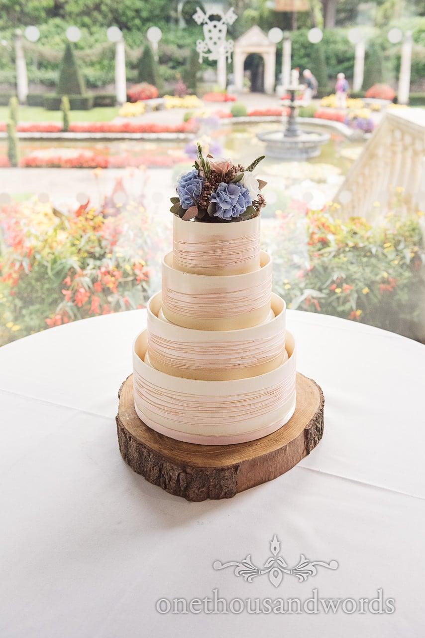 Flower topped wedding cake sitting pretty at Italian Villa Wedding venue photos