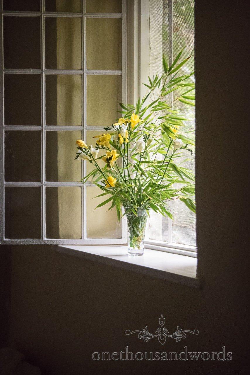 Flowers lit up by sunlight in window from Dorset garden wedding