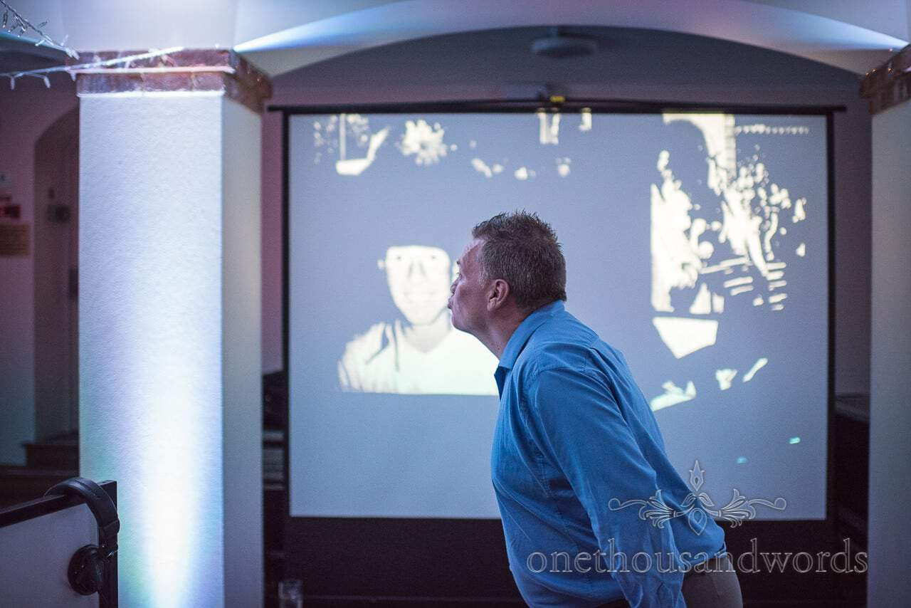 Funny guest poses with projected image at Italian Villa Wedding