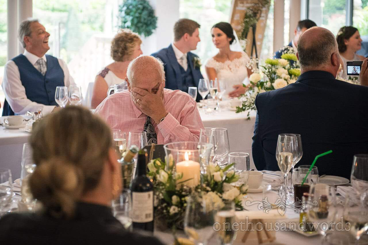 Grandfather buries his head in his hands during grandmother's wedding speech
