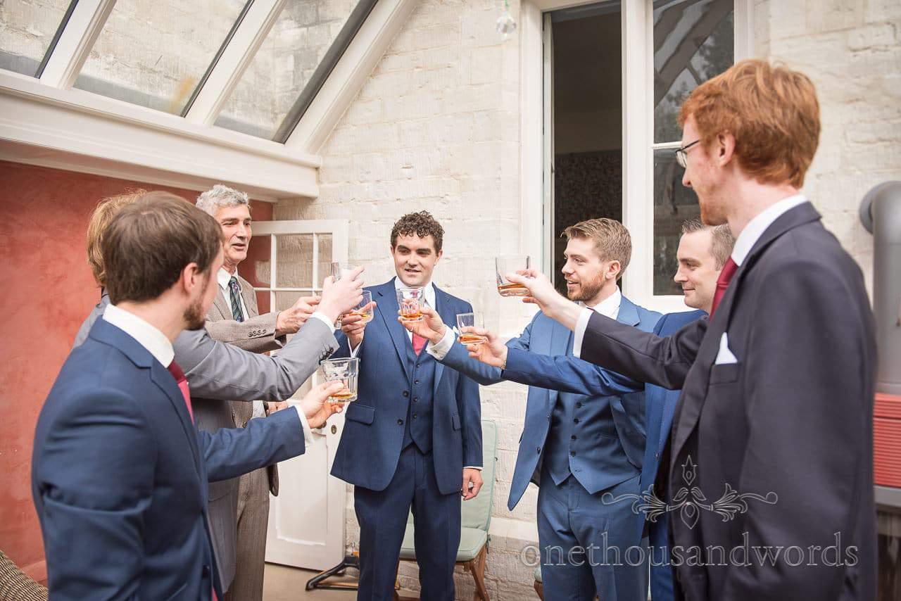 Groom and groomsmen raise a toast on morning of Dorset Garden Wedding