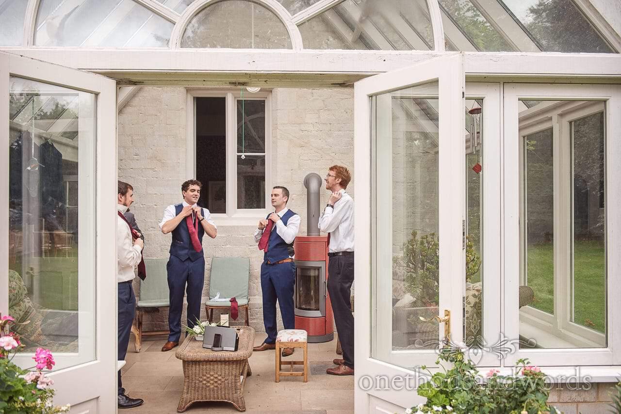 Groom and groomsmen tie their ties in conservatory before garden wedding
