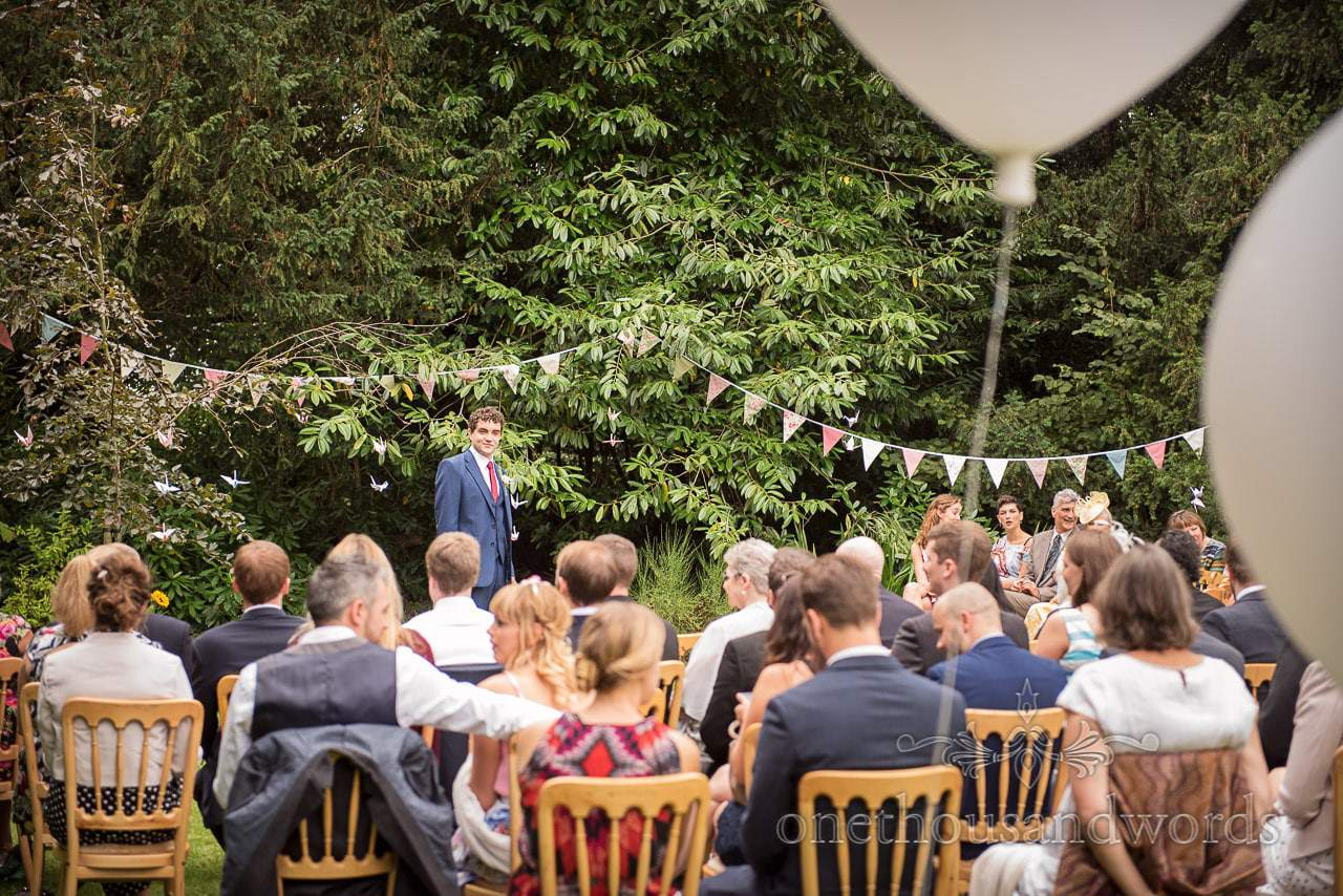 Groom awaits the arrival of the bridal party at Dorset garden wedding