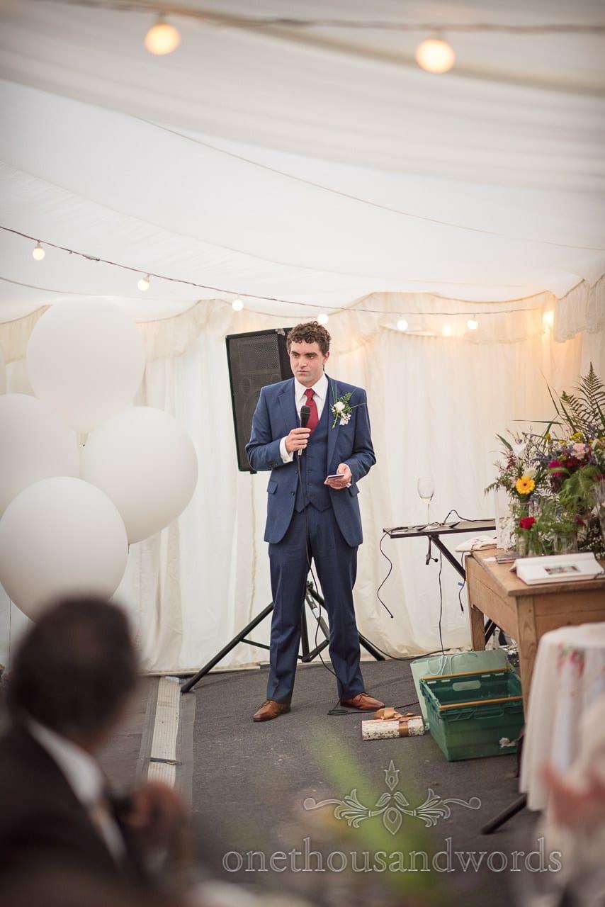 Groom delivers speech in marquee at Dorset garden wedding