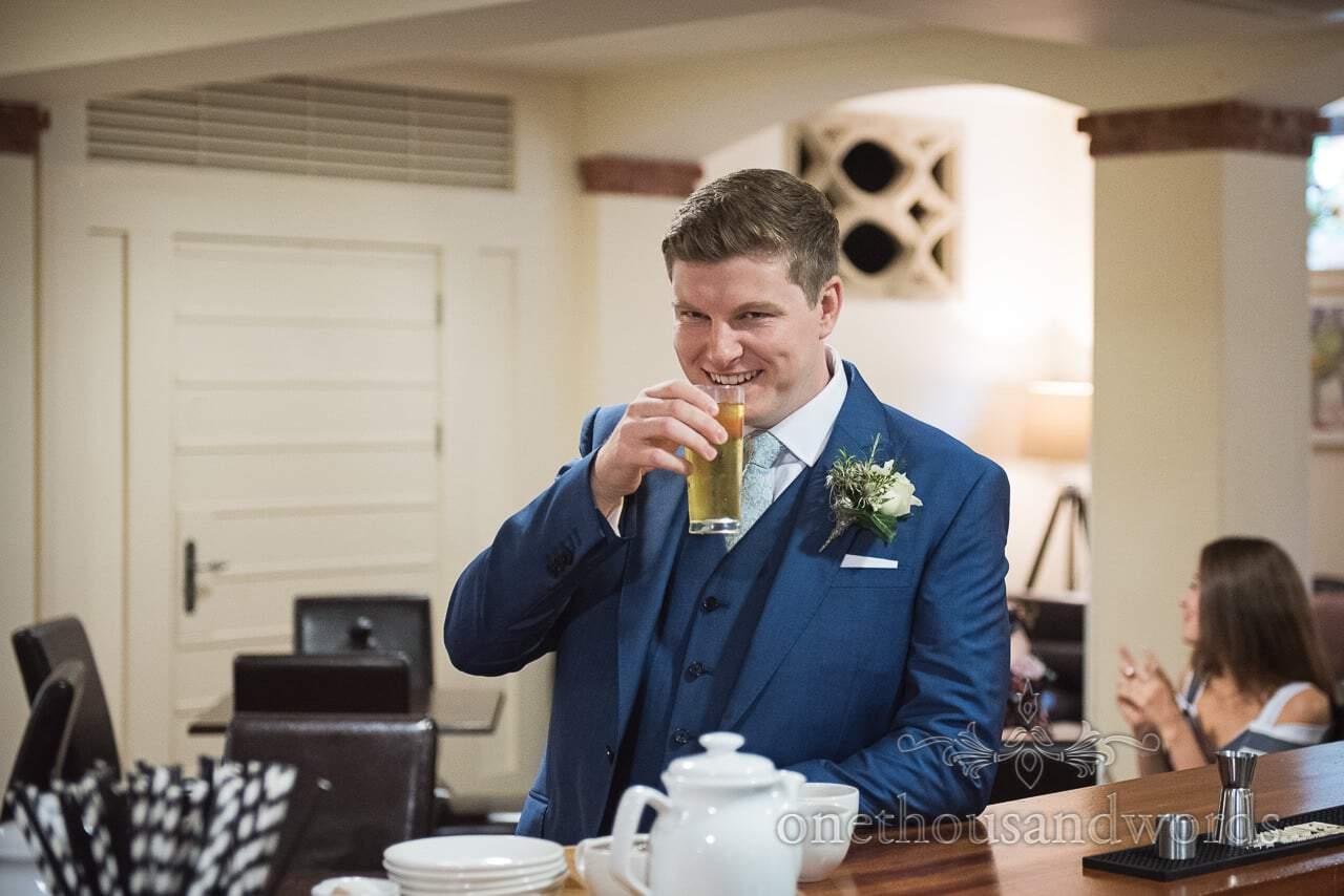 Groom enjoys a small glass of dutch courage at Italian Villa Wedding venue