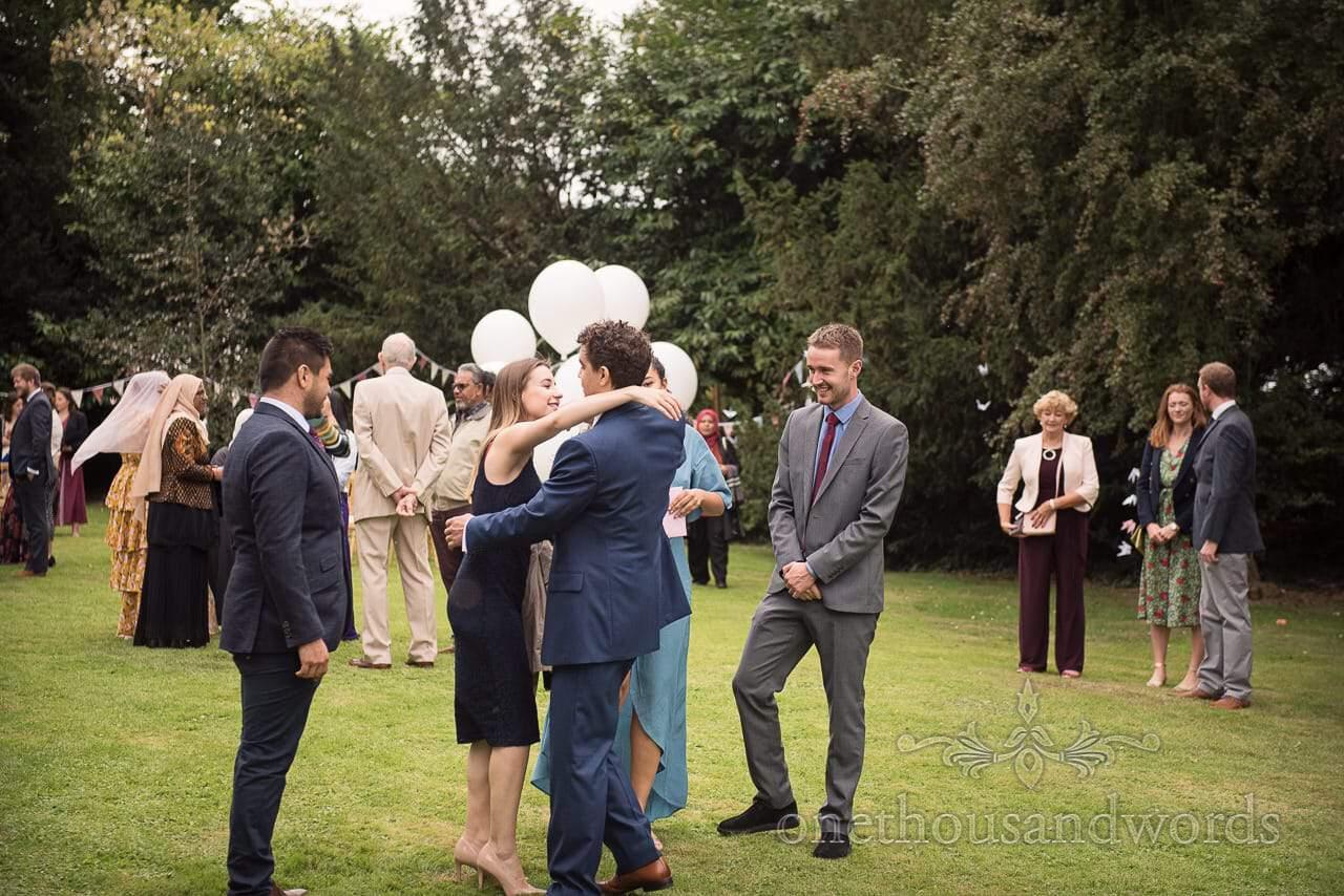 Groom greets guests before garden wedding ceremony