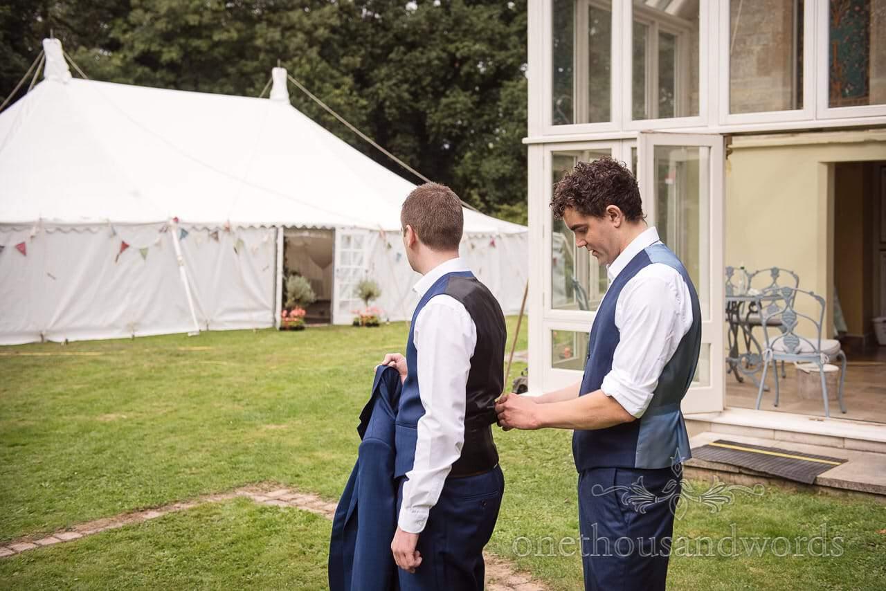 Groom helps groomsman with waistcoat at Dorset Garden Wedding