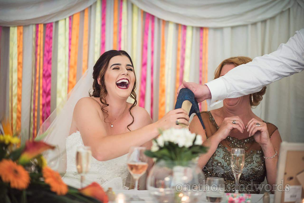 Groom passes pair of shoes to bride during speech at The Old Vicarage Wedding