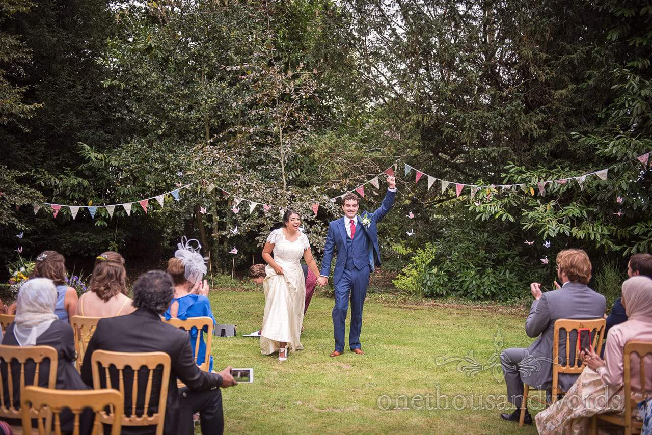 Groom punches the air in celebration at garden wedding