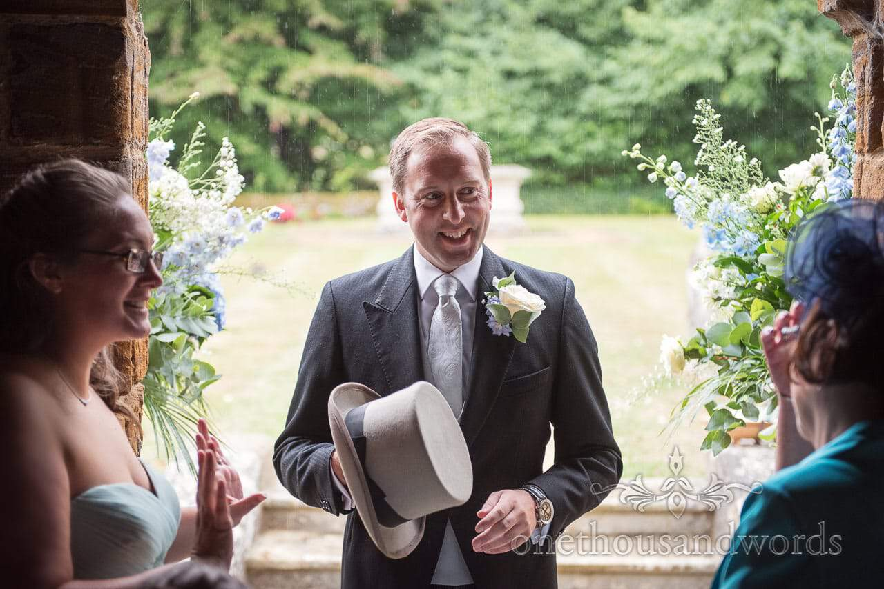Groom shelters from the rain outside church at Canford School Wedding