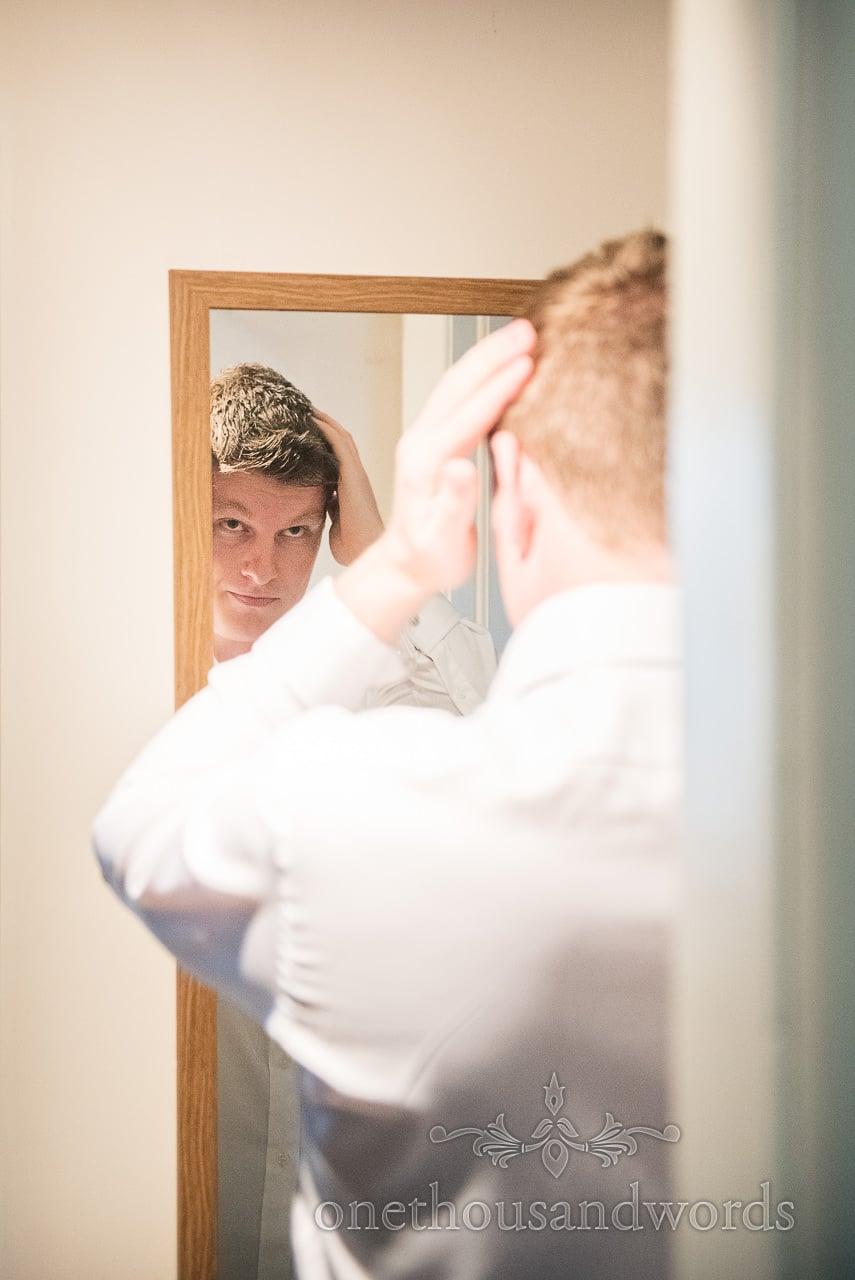 Groom styles hair in mirror on morning of Italian Villa Wedding